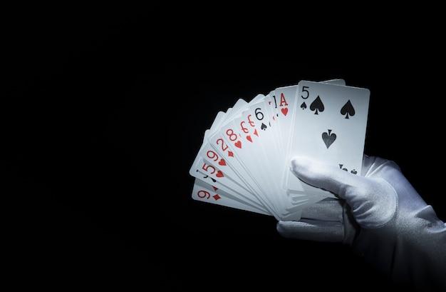 Mão do mago segurando ventilado cartas de jogar contra o fundo preto Foto gratuita