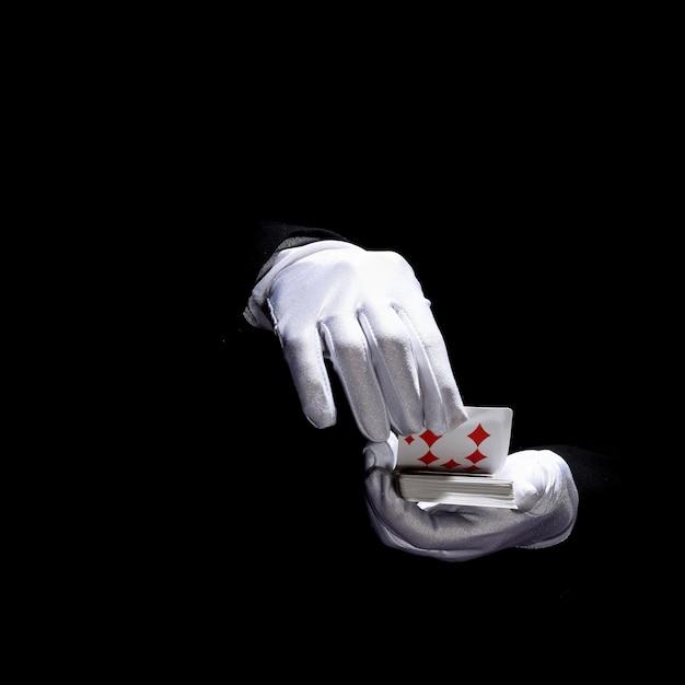 Mão do mago usando luvas brancas, segurando cartas de jogar contra o fundo preto Foto gratuita