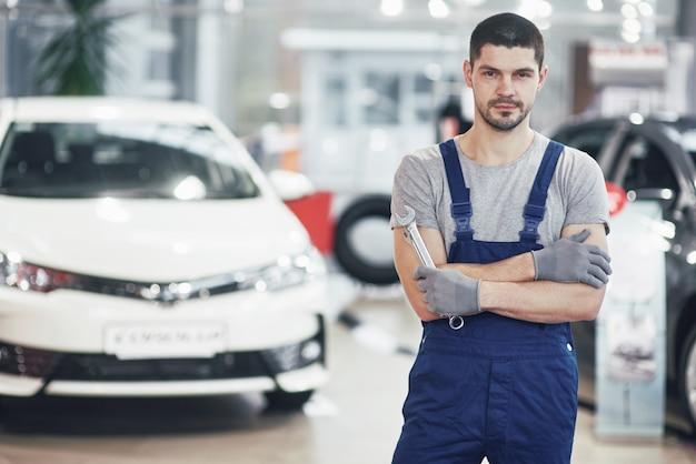Mão do mecânico de automóveis com chave. oficina de reparação automóvel Foto gratuita