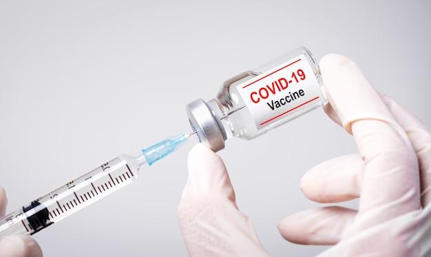 Mão do médico segurando a seringa e a vacina covid-19. conceito de cuidados de saúde e médicos. Foto Premium