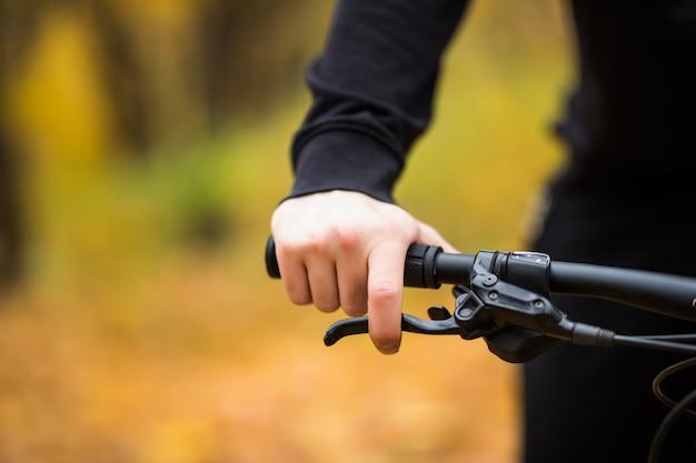 Mão do motociclista no guidão enquanto passeio no parque outono fechar Foto gratuita