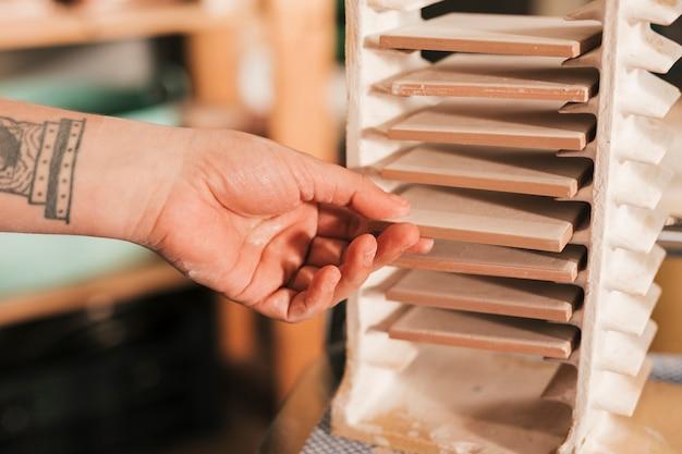 Mão do oleiro feminino removendo as telhas do rack Foto gratuita