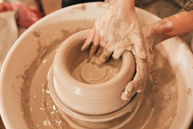 Mão do oleiro feminino sujo modelagem de argila em uma roda de oleiro Foto gratuita
