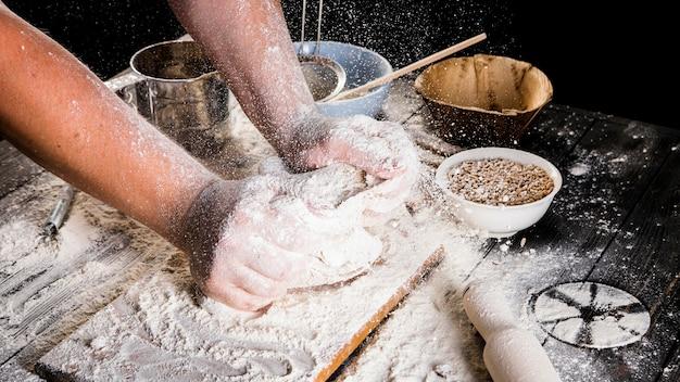 Mão do padeiro masculino amassar a massa sobre a mesa da cozinha Foto gratuita