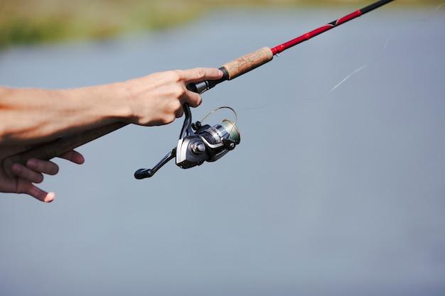 Mão do pescador pesca no fundo desfocado Foto gratuita