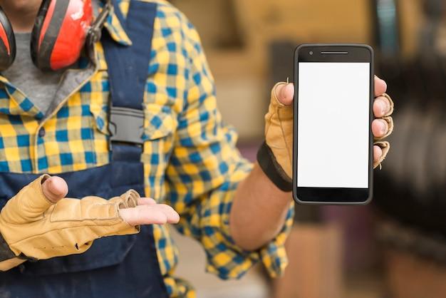 Mão do trabalhador manual, mostrando smartphone com tela branca Foto gratuita