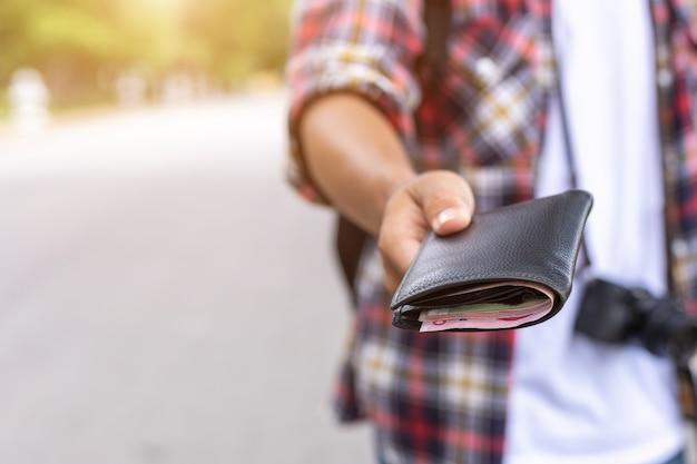 Mão do turista asiático que dá a cédula e a carteira preta que encontrou na atração turística. Foto Premium
