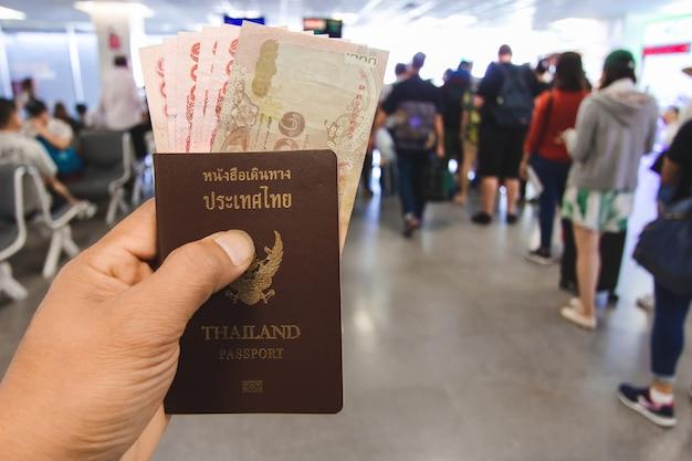 Mão do viajante detém dinheiro e passaportes na tailândia Foto Premium