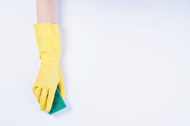 Mão do zelador com luvas amarelas segurando a esponja no fundo branco Foto gratuita