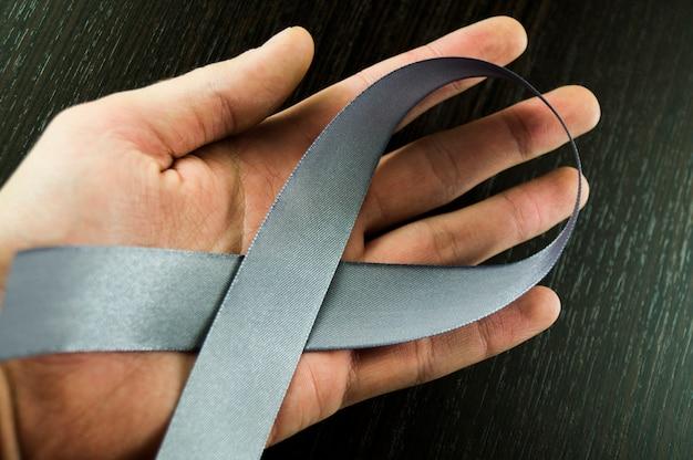 Mão dos homens do dia de parkinson com fita cinzenta Foto Premium