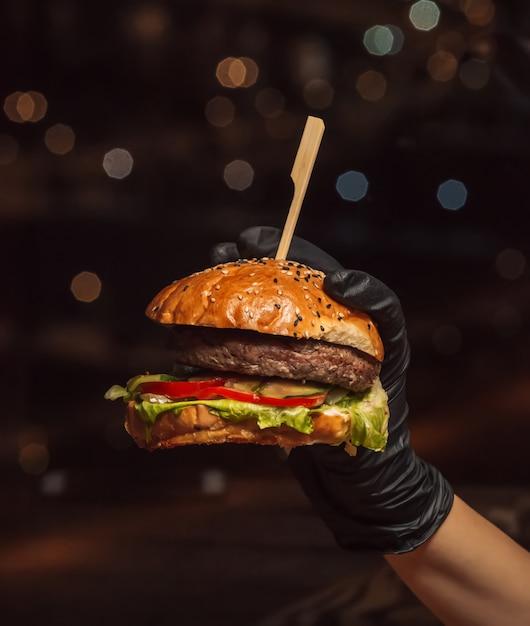 Mão em luvas de hambúrguer, segurando o hambúrguer de carne no fundo preto Foto gratuita