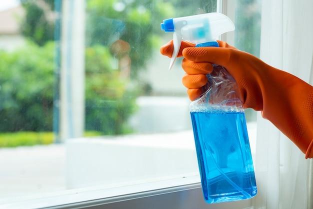 Mão em luvas laranja, limpando o painel da janela com spray conceito de limpeza evite várias infecções por vírus Foto Premium