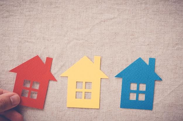 Mão escolhendo a propriedade de casa certa, conceito de busca de casa, seguro de casa Foto Premium