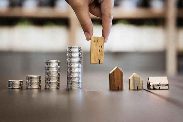 Mão escolhendo mini casa de madeira e linha de moedas na mesa de madeira Foto Premium