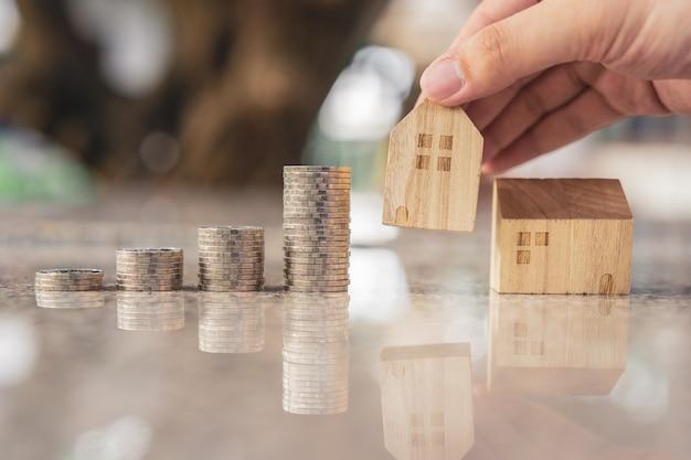Mão escolhendo mini modelo de casa de madeira do modelo e linha de dinheiro moeda na mesa de madeira Foto Premium