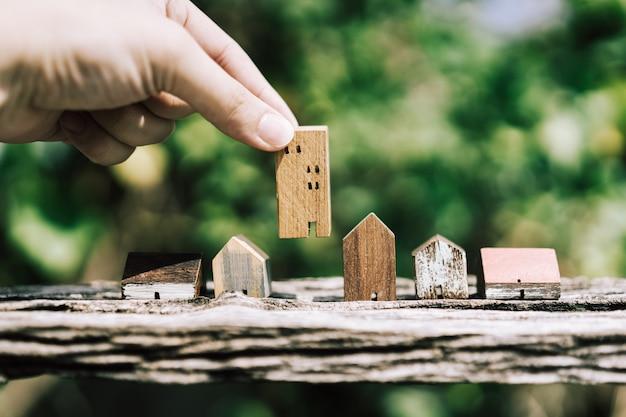 Mão escolhendo mini modelo de casa de madeira do modelo na mesa de madeira, Foto Premium