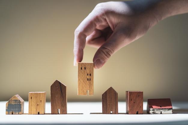 Mão, escolher, mini, casa madeira, modelo, de, modelo, e, fila, de, moeda dinheiro, ligado, tabela madeira Foto Premium