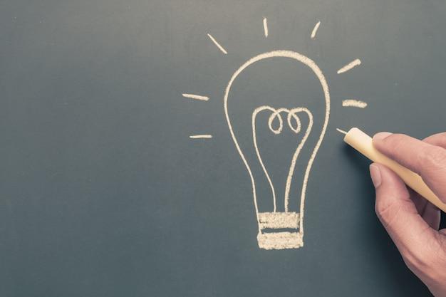 Mão escrevendo lâmpada no quadro-negro Foto Premium