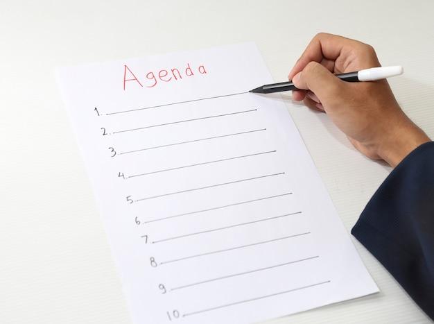 Mão escrevendo lista de agenda de negócios Foto Premium