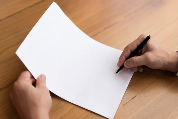 Mão escrevendo no papel vazio Foto gratuita