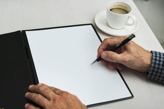 Mão, escrita, em, em branco, papel, perto, xícara café Foto gratuita