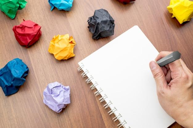 Mão, escrita, em, livro branco em branco aberto, pasta, livro branco, e, lápis, com, grupo, de, coloridos, papel Foto Premium