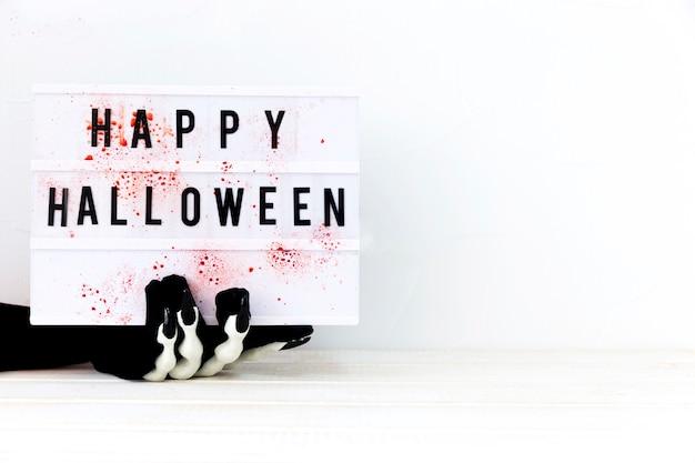 Mão esqueleto, segurando, tábua, com, feliz, dia das bruxas, escrita Foto gratuita
