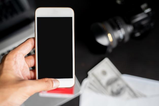 Mão esquerda, segurando, smartphone, ligado, borrão blackground, com, laptop, dólares, câmera, e, cartão crédito Foto Premium