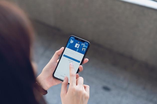 Mão está pressionando a tela do facebook no telefone inteligente da apple, mídias sociais estão usando para compartilhamento de informações e redes. Foto Premium