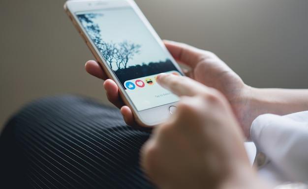 Mão está pressionando a tela do facebook no telefone. Foto Premium