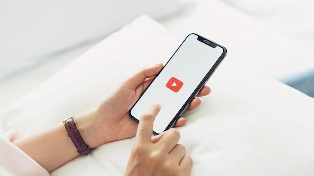 Mão está pressionando a tela exibe os ícones do aplicativo youtube no iphone da apple. Foto Premium
