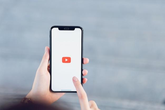 Mão está pressionando a tela exibe os ícones do aplicativo youtube Foto Premium