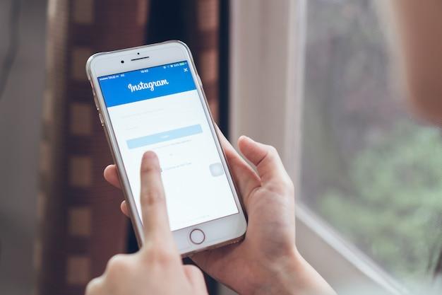 Mão está pressionando os ícones do instagram de tela de logon no apple iphone 6 Foto Premium