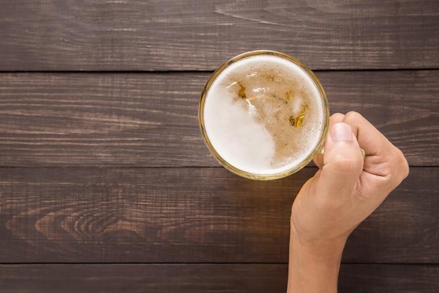 Mão está segurando um copo de cerveja no pub Foto Premium