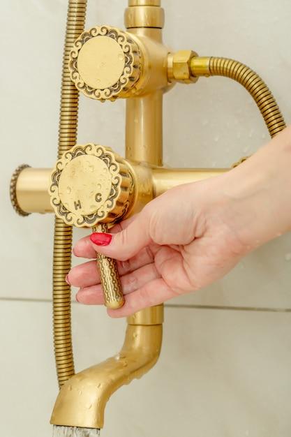 Mão famale alterna uma torneira de chuveiro em estilo vintage água fria e quente Foto Premium