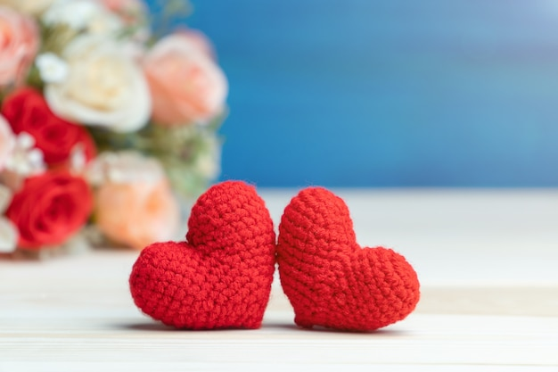 Mão faz dois fios coração vermelho na frente do buquê de flores rosa na mesa de madeira e fundo azul Foto Premium