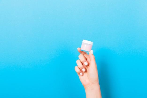 Mão fêmea que mantém a loção de creme da garrafa isolada. menina dar jar produtos cosméticos em azul Foto Premium