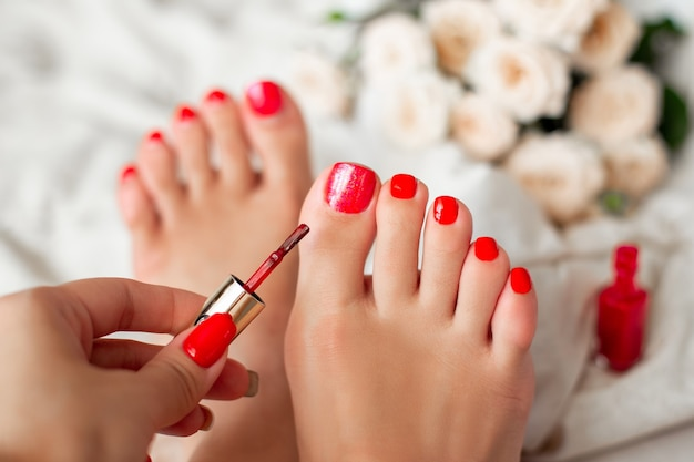 Mão feminina aplicando esmalte de gel vermelho nas unhas Foto Premium