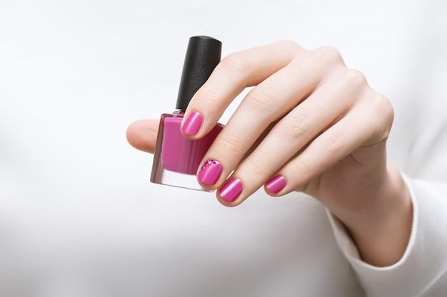 Mão feminina com design de unhas rosa segurando o frasco de esmalte Foto gratuita