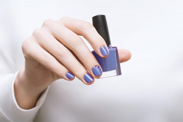 Mão feminina com design de unhas roxas, segurando o frasco de esmalte Foto gratuita