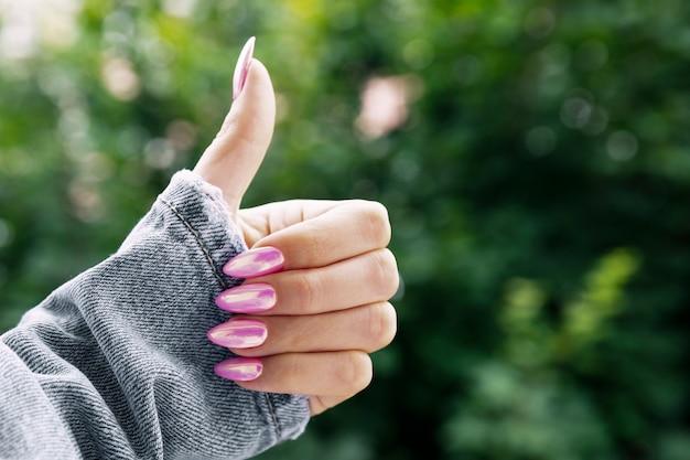 Mão feminina com uma bela manicure rosa mostra classe. Foto Premium