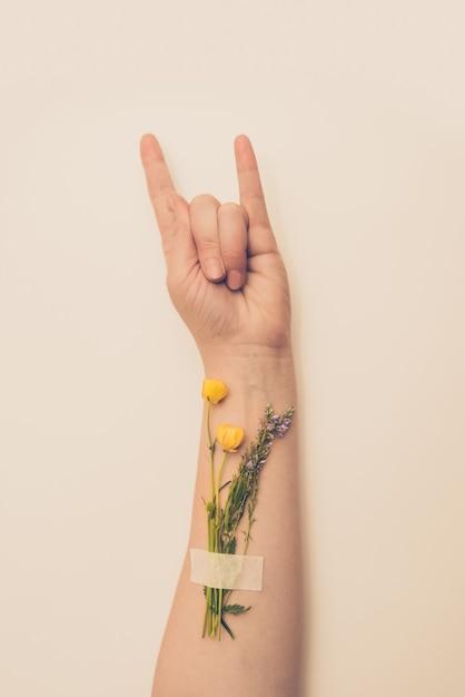 Mão feminina mostrando gesto de chifres com flores no pulso Foto Premium