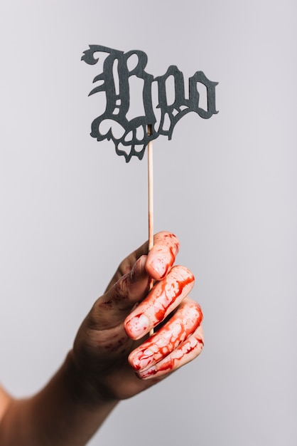Mão feminina sangrenta segurando sinal de boo Foto gratuita