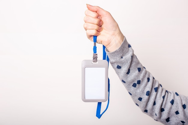 Mão feminina segura crachá, crachá, identificador de crachá, cordão na parede de luz Foto Premium