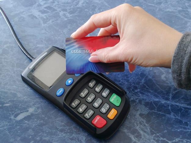 Mão feminina segura um cartão de crédito no terminal de pagamento. máquina de caixa para retiradas de dinheiro. tecnologia nfc. finanças e maneira sem dinheiro de pagar pela compra. Foto Premium