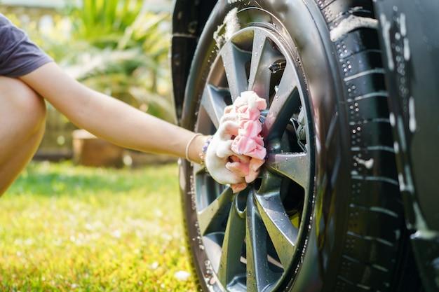 Mão feminina segura um pano de microfibra para lavar o carro. desinfecção de conceito e limpeza anti-séptica Foto Premium