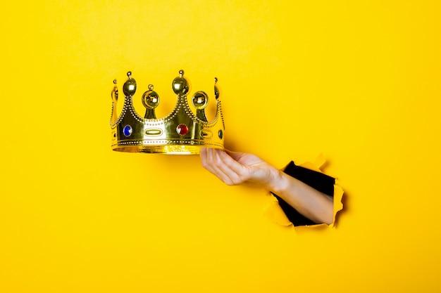 Mão feminina segura uma coroa de ouro em um fundo amarelo brilhante Foto Premium