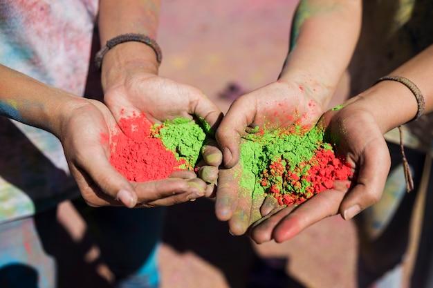 Mão feminina segurando cores holi vermelho e verde Foto gratuita