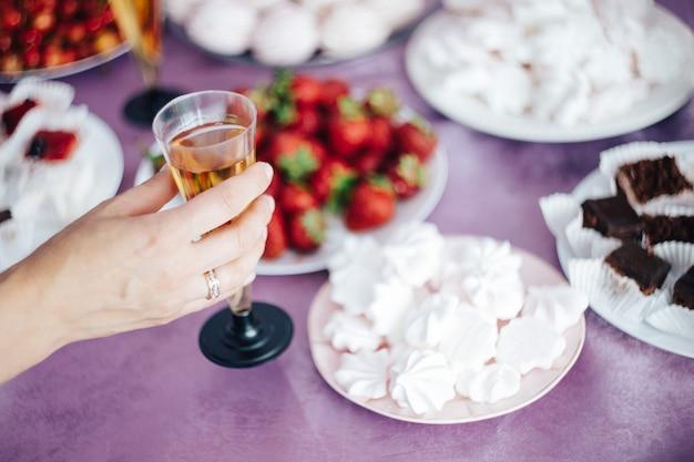 Mão feminina segurando uma taça de champanhe no fundo da mesa festiva Foto Premium