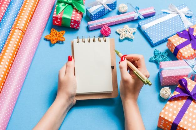 Mão feminina vista superior, fazendo algumas anotações no bloco de notas em azul. decorações de ano novo e brinquedos. época de natal Foto Premium